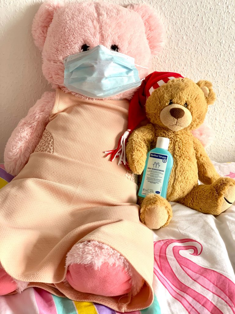 brown bear plush toy on pink and white textile